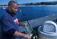 Recreational fisherman cutting his line on the commercial wharf in Monterey Bay, California.