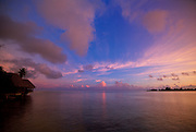 A view of the setting sun over the ocean from a vacation hut in Tahiti