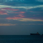 Two container ships anchored in Panama Bay before dawn awaiting their scheduled turn to enter the Panama Canal.