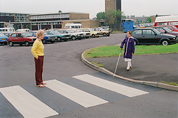 Teacher supervising young girl with visual impairment learning how to cross road on zebra crossing using white stick,
