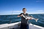 Proud boy with fish caught on deep sea fishing excursion.