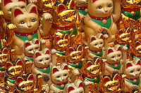 """The Maneki Neko literally """"Beckoning Cat"""" is also known as Welcoming Cat, Lucky Cat, Money cat or Fortune Cat.  They are common Japanese decorations, made of porcelain or ceramic,  which is believed to bring good luck to the owner. The sculpture depicts a cat usually  a Japanese Bobtail beckoning with an upright paw, and is usually displayed at the entrance of shops, restaurants  and other businesses. Some of the sculptures are electric and have a slow moving paw beckoning. In the design of the sculptures, a raised right paw supposedly attracts money, while a raised left paw attracts customers."""