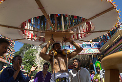 © Licensed to London News Pictures. 03/02/2015. Ipoh, Malaysia. A devotee with metal sticks pieced through his mouth carrying a kavadi dances in front of Kallumalai Murugan Temple in Ipoh, Malaysia, during the Thaipusam Festival,  Tuesday, Feb. 3, 2015. Photo credit : Sang Tan/LNP
