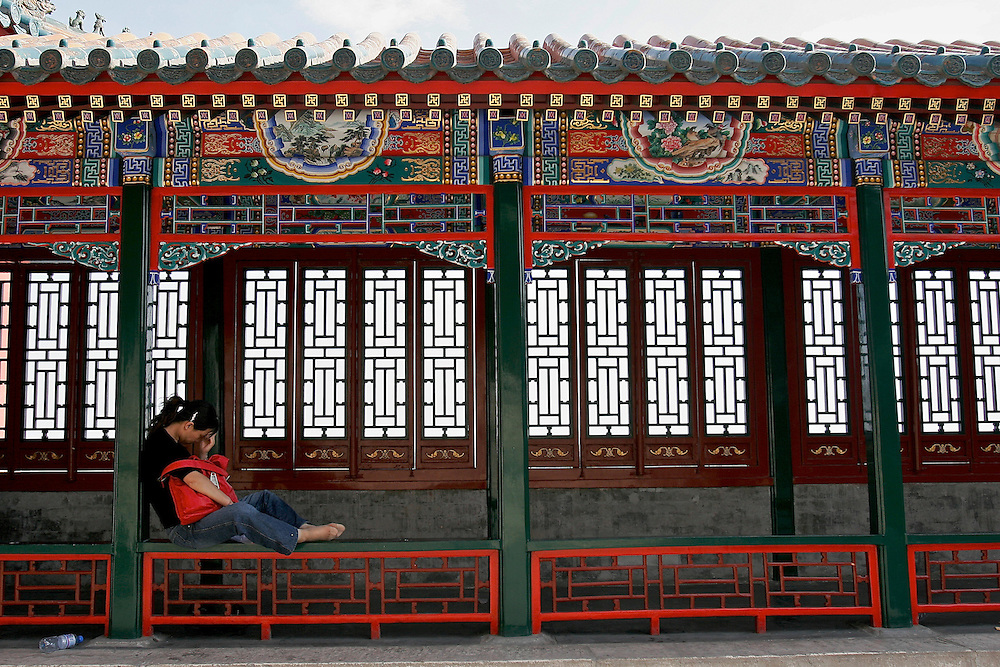A tourists to the Summer Palace rests at the top of the Tower of Buddhist Incense.  The Summer Palace in north west Beijing, China was built in the Jin Dynasty.  The Summer Palace is over 700 acres, 3/4 of which is the Kunming Lake.