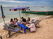 """26 SEPTEMBER 2014 - PATTAYA, CHONBURI, THAILAND: A vendor sells lottery tickets to Thais relaxing on Pattaya Beach. Pataya, a beach resort about two hours from Bangkok, has wrestled with a reputation of having a high crime rate and being a haven for sex tourism. After the coup in May, the military government cracked down on other Thai beach resorts, notably Phuket and Hua Hin, putting military officers in charge of law enforcement and cleaning up unlicensed businesses that encroached on beaches. Pattaya city officials have launched their own crackdown and clean up in order to prevent a military crackdown. City officials have vowed to remake Pattaya as a """"family friendly"""" destination. City police and tourist police now patrol """"Walking Street,"""" Pattaya's notorious red light district, and officials are cracking down on unlicensed businesses on the beach.     PHOTO BY JACK KURTZ"""
