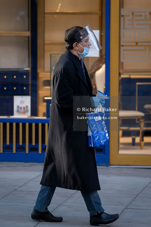 A shopper walks down Oxford Street as the second lockdown of the Coronavirus pandemic comes to a end, and a day before London enters the Tier 2 restriction when retailers will be allowed to once again re-open for the run-up to Christmas, on 1st December 2020, in London, England.