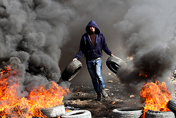 January 13, 2017 - Nablus, West Bank, Palestinian Territory - A Palestinian protester carries tires during clashes with Israeli security forces following a demonstration against the expropriation of Palestinian land by Israel in the village of Kfar Qaddum, near Nablus, in the occupied West Bank. (Credit Image: © Nedal Eshtayah/APA Images via ZUMA Wire)