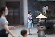 A woman praying  in the Jing'an Temple courtyard , Shanghai, China