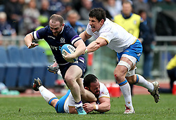 Scotland's Nick Grigg is tackled during the NatWest 6 Nations match at the Stadio Olimpico, Rome.