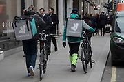 Deliveroo cycle couriers with their large back boxes while out delivering in London, England, United Kingdom.