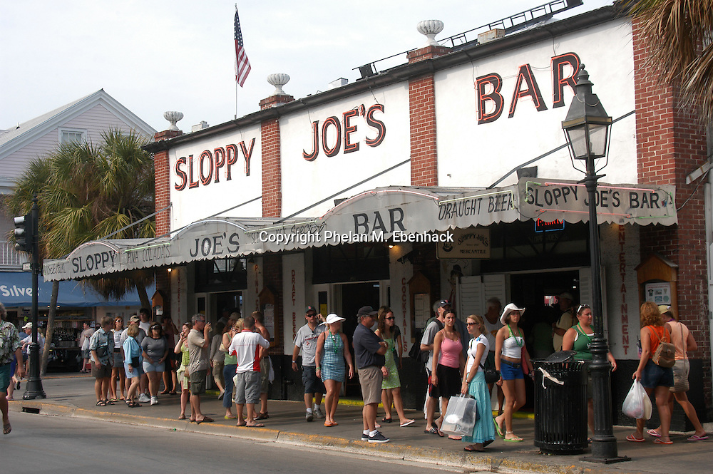 Tourists walk past the famous Sloppy Joe's Bar on Duval St. in Key West, Florida.