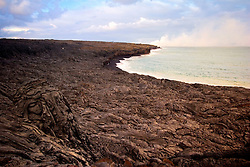 Brand new land and black sand beach created by a series of eruption between 2003 to present, steam clouds visible at distance, Hawaii Volcanoes National Park at night, Kilauea, Big Island, Hawaii..