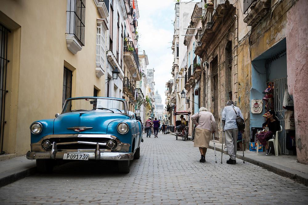 Two elderly people walk past an old American car in Habana Vieja, the historic heart of Havana, Cuba