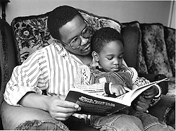 Father wearing glasses reading story to son,