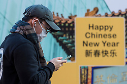 © Licensed to London News Pictures. 05/02/2021. LONDON, UK. A man wearing a facemask checks his mobile phone near a construction hoarding in Chinatown ahead of the Chinese New Year festival, the Year of the Ox.   The normal parade and festivities have been cancelled this year due to the ongoing coronavirus pandemic and the organisers will instead host celebrations online.  Photo credit: Stephen Chung/LNP