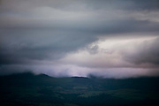Views of a storm over Snowdonia across the Menai Strait from Penmon  village on the south-east tip of the Isle of Anglesey in Wales.