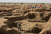 Women make bricks for more stubstantial housing in the scorched barren dirt of the 4 sq km camp Abu Shouk refugee camp which is (disputedly) home to 38,000 displaced persons and families on the outskirts of the front-line town of Al Fasher (also spelled, Al-Fashir) in north Darfur. .