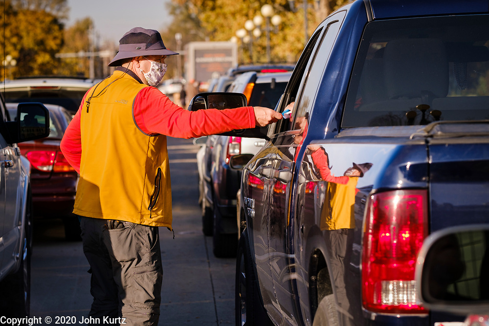06 NOVEMBER 2020 - DES MOINES, IOWA: A volunteer hands paperwork to a client during an emergency food distribution at the Iowa State Fairgrounds Friday. A spokesperson for the Food Bank of Iowa said they had enough food for 1,500 families. Each family got frozen chicken legs, frozen liquid eggs, and fresh produce. There will be another emergency food distribution at the Fairgrounds on November 30. Food insecurity in the Des Moines area has skyrocketed since the start of the Coronavirus pandemic. Although unemployment rates in Iowa have fallen since a peak in June, many families that fell behind on rent are now facing eviction. The food bank spokesperson said use of the Food Bank's emergency pantries and distribution points is still increasing.    PHOTO BY JACK KURTZ