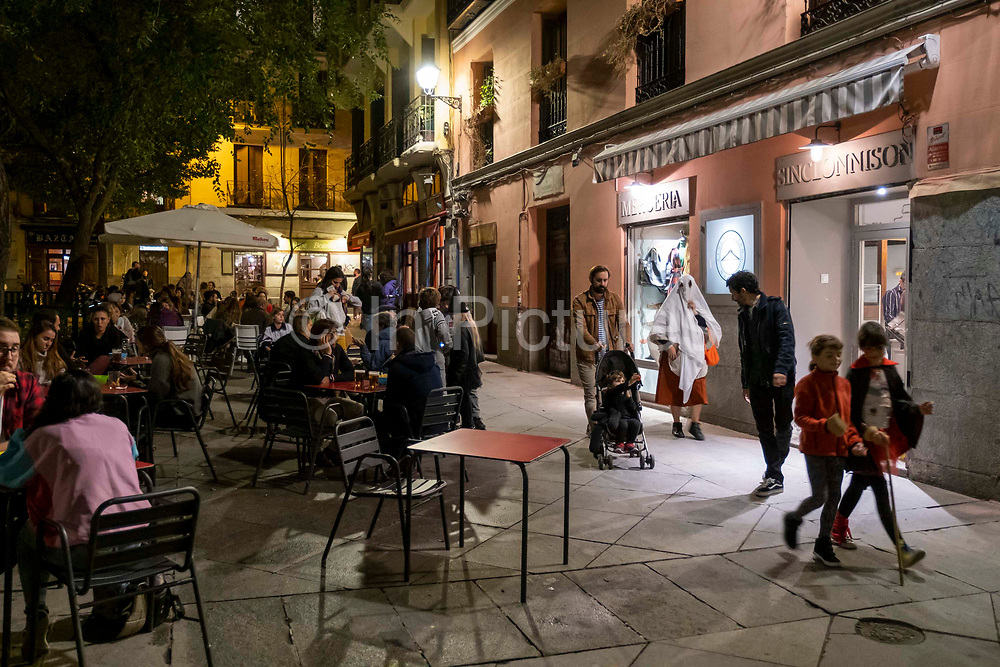 A woman dressed as a ghost walks past people sitting outside eating dinner and having drinks at a bar on the Plaza del Dos de Mayo during the Halloween celebrations on the 31st of October 2019 in Madrid, Spain.