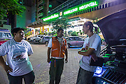 "30 NOVEMBER 2012 - BANGKOK, THAILAND: Volunteer medics with the Ruamkatanyu Foundation leave Camillan Hospital, a nonprofit hospital run by Italian monks, after dropping off a patient during a Friday night shift. The Ruamkatanyu Foundation was started more than 60 years ago as a charitable organisation that collected the dead and transported them to the nearest facility. Crews sometimes found that the person they had been called to collect wasn't dead, and they were called upon to provide emergency medical care. That's how the foundation medical and rescue service was started. The foundation has 7,000 volunteers nationwide and along with the larger Poh Teck Tung Foundation, is one of the two largest rescue services in the country. The volunteer crews were once dubbed Bangkok's ""Body Snatchers"" but they do much more than that now.    PHOTO BY JACK KURTZ"