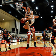Azusa Pacific forward Jake Spurgeon (4) hangs in the air as he puts up a shot on Biola forward Solomon Ruddell (32) during the PacWest basketball championships semifinals in the Felix Event Center at Azusa Pacific University Friday, Mar. 6, 202, in Azusa. (Mandatory Credit: Christina Leung-Sports Shooter Academy)