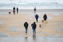 People enjoy a brisk walk on a cold, windy  day at Fistral Beach in Newquay, Cornwall.