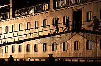 Sillouettes of guests boarding the ship in strong, golden morning light.