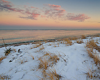 Snow covers the sand dunes at Illinois Beach State Park shortly after sunset. The soft colors of the sky in the east was reflecting on the calm Lake Michigan.