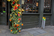 Alongside a floral display over the doorway of the Angel & Crown pub, stand two remaining gas cylinders after a delivery of new stock to its cellar on St. Martin's Lane,  on 15th June 2019, in London, England.