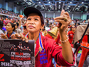 "23 FEBRUARY 2014 - NAKHON RATCHASIMA (KORAT), NAKHON RATCHASIMA, THAILAND:  A woman cheers for Red Shirt speakers in Korat. The United front of Democracy against Dictator (UDD or Red Shirts), which supports the elected government of Yingluck Shinawatra, staged the ""UDD's Sounding of the Battle Drums"" rally in Nakhon Ratchasima (Korat) to counter the anti-government protests that have gripped Bangkok since November. Around 4,000 of UDD's regional and provincial coordinators along with the organization's core members met at Liptapunlop Hall inside His Majesty the King's 80th Birthday Anniversary Sports Complex in Korat to discuss the organization's objectives and tactics against anti-government protestors, which the UDD says ""seek to destroy the country's democracy."" The UDD leadersa announced that they will march to Bangkok and demonstrate against anti-government protests led by Suthep Thaugsuban.  PHOTO BY JACK KURTZ"