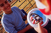 NOV 18, 2001 _ GILBERT, AZ, USA: Mark Saba, 15, from Chandler, helps Jeff Hanger, 12, also from Chandler, check his patriotic clown face before the Lil' Dude youth rodeo during the Gilbert Days rodeo in Gilbert, AZ, Sunday, Nov. 18, 2001. PHOTO BY JACK KURTZ