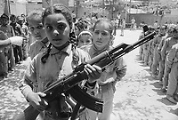 1970, Beirut, Lebanon --- Young girl holding a machine gun, with other children in training as commandos, at a Palestinian refugee camp which gave strong support to Al Fatah, the pre-PLO (Palestine Liberation Organization) group of which Yassir Arafat was the leader. --- Image by © Owen Franken/CORBIS