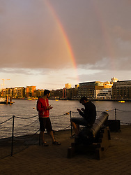 © Licensed to London News Pictures. 06/07/2014. London, UK. A rainbow is seen from St Katharine Docks near Tower Bridge looking east down the River Thames this evening just before sunset. Photo credit : Vickie Flores/LNP