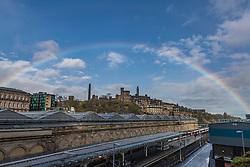 A rainbow over the city of Edinburgh. The rainbow arches over the Waverley train station and Calton Hill