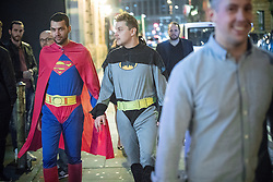© Licensed to London News Pictures . 29/10/2016 . Manchester , UK . Two men , one wearing a Batman costume and the other a Superman costume , hold hands as they walk along Peter Street . Revellers on a night out , many in fancy dress , on the weekend before Halloween . Photo credit : Joel Goodman/LNP