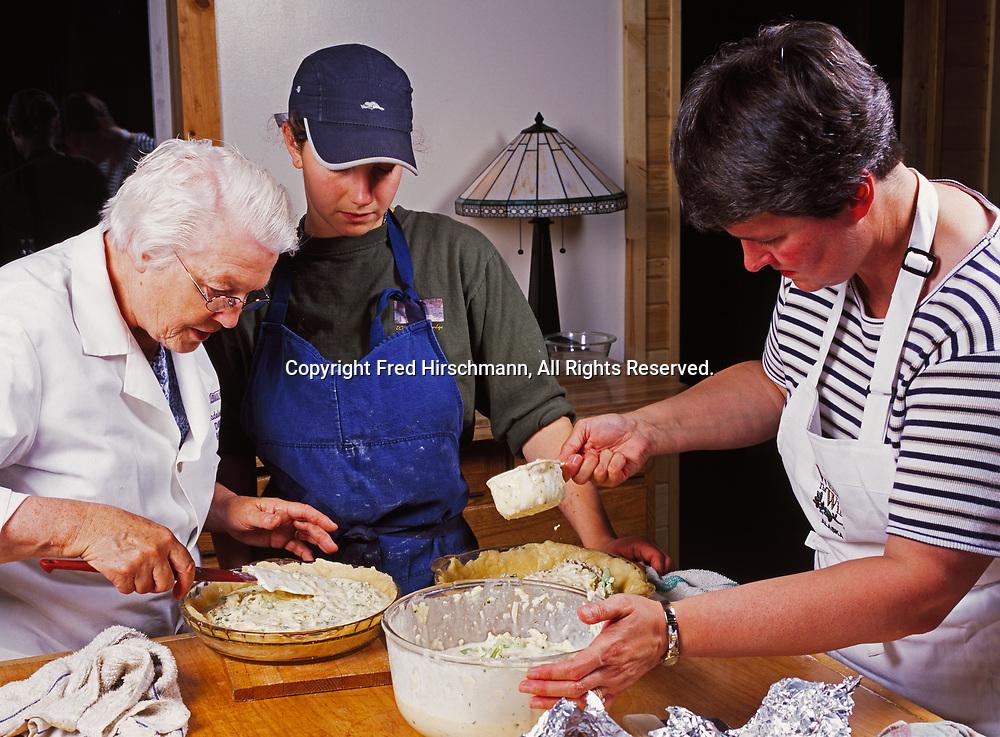 Madeleine Kamman, Sara Spudowski and Patty Park filling quiche, cooking seminar at Kirsten and Carl Dixon's Winterlake Lodge, Alaska.  (Model Released)