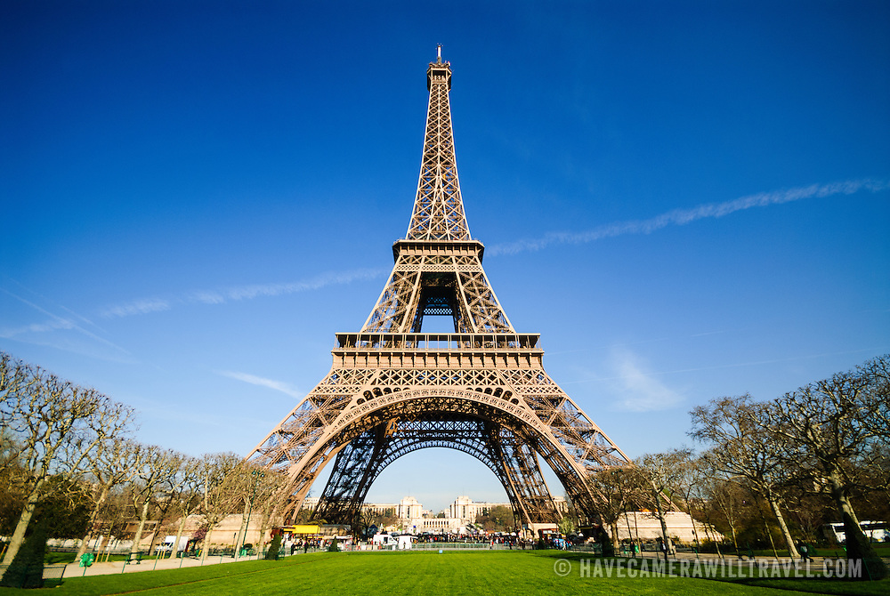 A wide-angle shot of the Eiffel Tower in Paris with a deep blue sky of a spring morning. This shot is taken from the Champ de Mars. Constructed for the 1889 World's Fair, it has become one of the world's most recognizable landmarks.