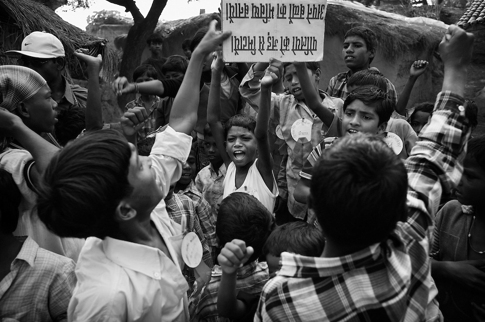 """Children lead a procession through the lanes of Hinduni Musahar village near Patna city. The procession, known as """"social barricading"""" carries a message calling for parents to vaccinate their children against polio before going to harvest. The residents of the village and the children on the procession are from the very low-caste Musahar community. Without proper sanitation, and with literacy running at less than 2 percent, the Musahar are particularly susceptible to polio. They are one of the communities to which Unicef are directing their polio vaccination effort. ..India is one of only four countries in the world reported to suffer endemic polio. Only 66 new cases of the disease were reported in India in 2005. But in 2006 that figure leapt ten-fold. In September, UN Secretary General Kofi Annan wrote to Indian Prime Minister Manmohan Singh expressing concern at the new polio outbreak. The Indian government, together with partners including Unicef and Rotary International has embarked on a renewed effort to eradicate polio. Overcrowded areas of poor sanitation are particularly susceptible to the virus. Focusing on the poor north Indian states of Uttar Pradesh and Bihar which between them are home to more than 250 million people, Unicef is coordinating the largest public health drive in the world. The task is to vaccinate all children under the age of five during a series of vaccination rounds. Unicef has mobilised thousands of volunteers to administer and supervise the vaccination effort. Unicef has also recruited people with influence to encourage communities to have their children protected against polio. Misinformation, rumours and a frustration with the lack of other health services mean that many households, particularly in Muslim areas, resist vaccination. ..Photo: Tom Pietrasik.Patna, Bihar, India..November 16th 2006"""
