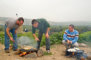 Outdoor Cooking Two Men preparing a flat bread Pita on a Saj - an iron dome shaped pan that is used to cook the pita bread on. It is placed over a source of heat, traditionally a wood fire, and the dough is placed on it to cook.
