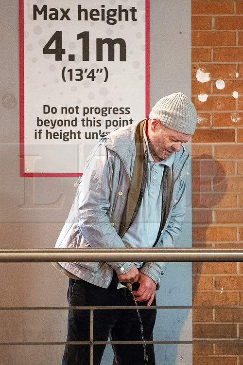 © Licensed to London News Pictures . 28/10/2018. Manchester, UK. A man urinates outside the Arndale Centre in Manchester City Centre . Revellers on a night out , many in fancy dress , on the weekend before Halloween . Photo credit: Joel Goodman/LNP