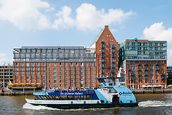 Passenger ferry boat and  warehouse buildings converted to luxury apartments and offices on waterfront of River Elbe in Hamburg Germany