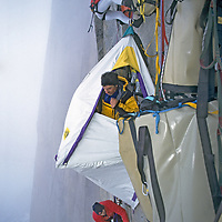 BAFFIN ISLAND, NUNAVUT, CANADA. Jon Catto, Greg Child & Mark Synnott (MR) set up a hanging Portaledge camp, high on upper headwall of Great Sail Peak, a 4,000-vertical-foot, overhanging granite wall.