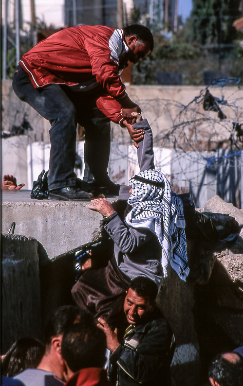 Jerusalem, wall of Abu Dis at the change of patrol. The simplest activities such as going to work or school, reaching the hospital or visiting relatives exposes women and men, children and the elderly to these risks that the Palestinians tend to limit their movements to what is absolutely indispensable.<br /> Jerusalem, January 2004<br /> <br /> <br /> Photo: Antonietta Baldassarre