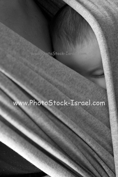 A young one month baby carried close to his mother's bosom in a blanket wrap