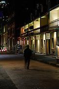 Lone pedestrian walking through The Rocks at night. The Rocks, Sydney, Australia