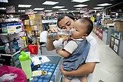 Father giving his child a drink inside e-plaza digital square shopping mall. Zhongguancun or Zhong Guan Cun, is a technology hub in Haidian District, Beijing, China. It is situated in the northwestern part of Beijing city. Zhongguancun is very well known in China, and is often referred to as China's Silicon Valley. This is Beijing's computer district with numerous tech companies offices situated here amongst the many malls which sell electronics and electrons equipment of all kinds. The tech park started as a small office where two decades ago some students from a nearby university decided that computer equipment may be a thing of the future so set up a small company. It has expanded in this time to  cover many square kilometres.