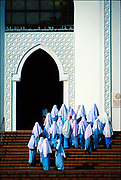 Muslim women in scarves and prayer robes ascend the steps of Malaysia's National Islamic Center. Malaysia, which boasts one of Southeast Asia's most vibrant economies, has a Muslim-majority population  61.3 percent. Muslim Malays dominate the country's politics, and benefit from positive discrimination in business, education and the civil service, but an ethnic Chinese minority holds economic power. © Steve Raymer 2002 / ALL RIGHTS RESERVED