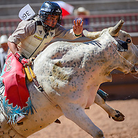 080515       Cable Hoover<br /> <br /> Bull rider Latrell Long leans in to stay balanced during the IJRA rodeo Wednesday at Red Rock Park in Gallup.