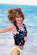 Woman running in surf, Hawaii