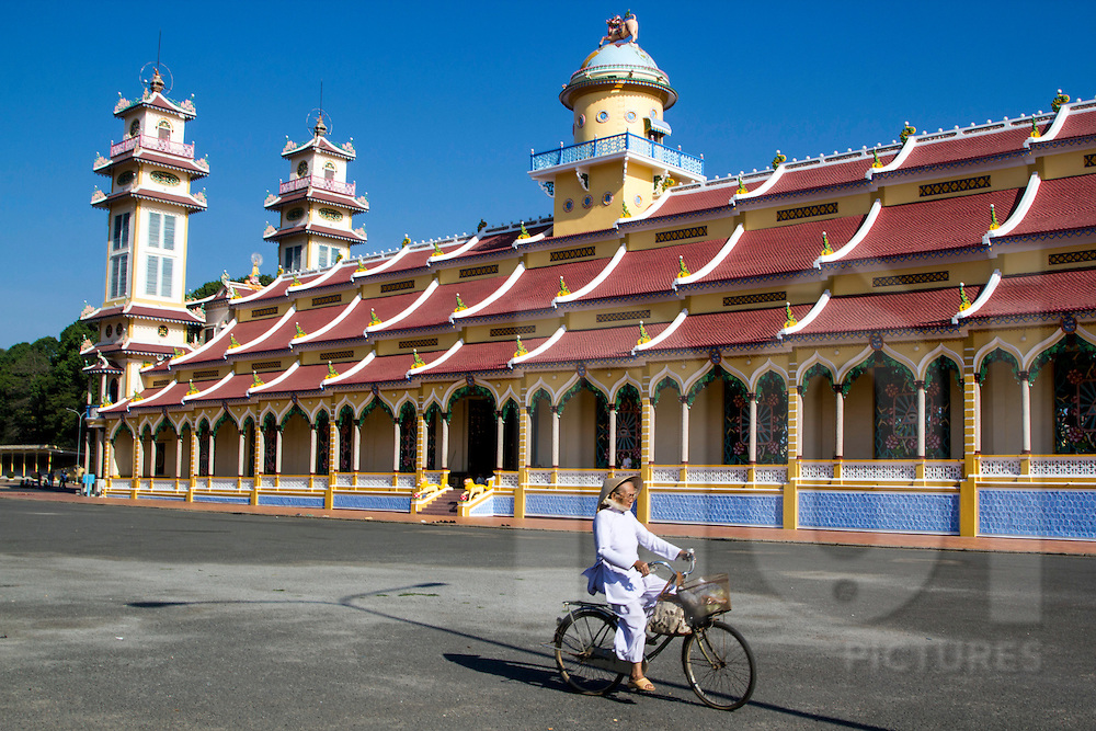 An old vietnamese woman on her bicycle rides in front of Cao Dai Temple, Tay Ninh, Vietnam, Southeast Asia